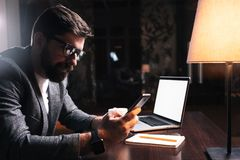 Young bearded businessman using phone while sitting by the wooden table in modern office at night. People working mobile devices. Coworking concept royalty free stock image