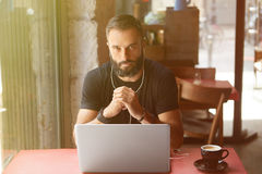 Young Bearded Businessman Wearing Black Tshirt Working Laptop Urban Cafe.Man Sitting Wood Table Cup Coffee Listening stock photos
