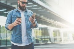 Young bearded businessman wearing sunglasses stands on city street, holds cup of coffee and uses smartphone. Royalty Free Stock Images