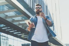 Young bearded businessman wearing sunglasses walking down city street, holding cup of coffee and tablet computer. stock image