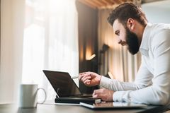 Young bearded businessman in white shirt is sitting at table in front of computer, showing pen on laptop screen. Freelancer working home. Online education royalty free stock images