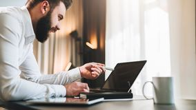 Young bearded businessman in white shirt is sitting at table in front of computer, showing pen on laptop screen. Freelancer working home. Online education stock photography