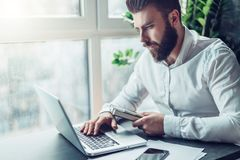 Young bearded businessman in white shirt is sitting at table and working on laptop. Freelancer works at home. Student. Is studyng online. Online marketing stock photography