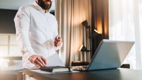 Young bearded businessman in white shirt is standing near desk in front of laptop, holding documents. Freelancer working. Home. Student learning online. Online royalty free stock images