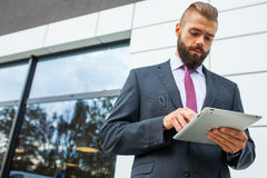 Young bearded businessman writting business e-mail using his tab Royalty Free Stock Image
