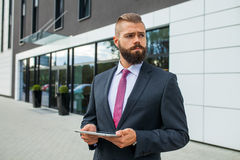 Young bearded businessman writting business e-mail using his tab Stock Photography