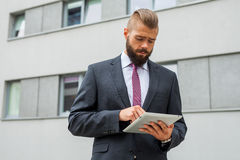 Young bearded businessman writting business e-mail using his tab Royalty Free Stock Images