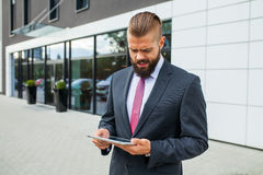 Young bearded businessman writting business e-mail using his tablet Royalty Free Stock Image