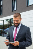 Young bearded businessman writting business e-mail using his tablet Stock Photography