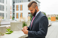Young bearded businessman writting business e-mail using his tablet Royalty Free Stock Images