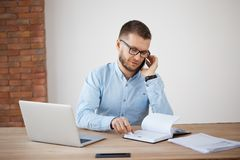 Young bearded caucasian manager in glasses and blue shirt talking with customer on phone, discussing order details Stock Photography