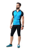 Young bearded cyclist guy in blue jersey t-shirt and leggings relaxed smiling and looking away Stock Photography