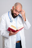 Young bearded doctor with book Royalty Free Stock Images
