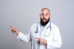 Young bearded doctor looking amazed and pointing to side Stock Photography