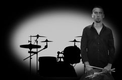 Young bearded drummer on drums silhouette background. Royalty Free Stock Photos
