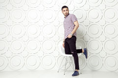 Young bearded fashion model in casual style is posing near white circle wall background. studio shot. Stock Photos