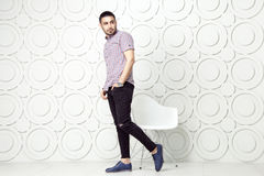 Young bearded fashion model in casual style is posing near white circle wall background. studio shot. Posing and looking away with hand on packet royalty free stock photos