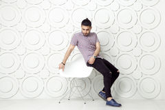 Young bearded fashion model in casual style is posing near white circle wall background. studio shot. Royalty Free Stock Images