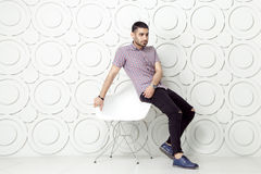 Young bearded fashion model in casual style is posing near white circle wall background. studio shot. Stock Image