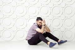 Young bearded fashion model in casual style is posing near white circle wall background. studio shot. Stock Photo
