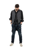Young bearded fashion model with hands in pockets looking down. Royalty Free Stock Image