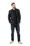 Young bearded fashion model looking up with hands in pockets Royalty Free Stock Images