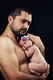 Young bearded father gently holds on his chest  newborn baby daughter Royalty Free Stock Photography