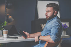 Young bearded freelancer man in denim shirt is sitting at home at table, holding mobile phone in his hand and thinking. Royalty Free Stock Images