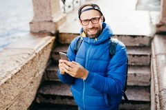 Young bearded guy in black cap and blue anorak holding rucksack standing outdoors with cell phone isolated over steps background. Stylish blogger with stock images
