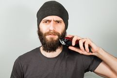 Young bearded guy in hat hold clipper and cut his beard. On gray background. Young bearded guy in hat hold clipper and cut his beard. On a gray background stock photo