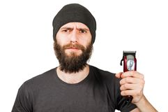Young bearded guy in hat hold clipper and cut his beard. Isolated on white background. Young bearded guy in hat hold clipper and cut his beard. Isolated on a stock image