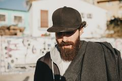 Young bearded guy portrait, with the sun in the face, with urban street style clothes and a black cap. Stock Image