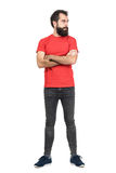 Young bearded guy in red t-shirt with crossed arms looking away Royalty Free Stock Photos