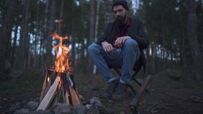 Young bearded guy sitting on the chair near fire. Forester by the bonfire in the forest.
