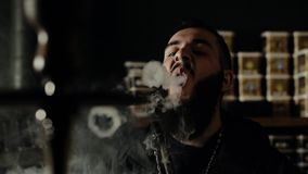 Bearded guy close up smoking hookah and makes rings of smoke in slow motion stock video footage
