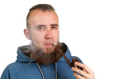 Young bearded guy smoking a pipe Stock Photography