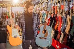 Young bearded guy stand and hold electric and acoustic guitars. He looks at blue one. Young hipster in alone in room royalty free stock photo