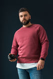 A young bearded handsome hipster man, dressed in a red pullover with long sleeves and jeans, stands indoors. And holds a camera in his hand. In the background Stock Image