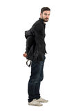 Young bearded handsome male model taking off black leather jacket Royalty Free Stock Photo