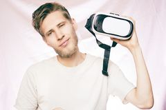 Young bearded handsome smiling man holding the vr glasses isolated royalty free stock image