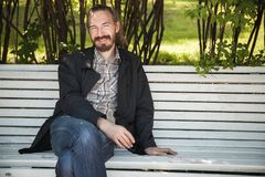 Young bearded happy man on white bench. In summer park, outdoor portrait Royalty Free Stock Photography