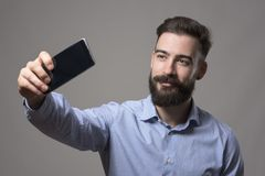 Young bearded hipster business man talking selfie photo with smart phone smiling and looking at phone. Against gray studio background Royalty Free Stock Photos