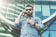 Young Bearded Hipster Businessman In Sunglasses And Stands Outdoor,drinking Coffee And Talks On His Cell Phone. Royalty Free Stock Photography