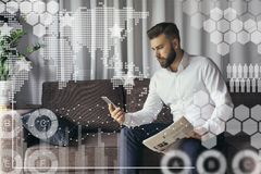 In foreground are virtual graphs,diagrams,charts.Man blogging online. Young bearded hipster businessman in white shirt is sitting on the sofa in recreation room Stock Photo