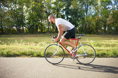 Young bearded hipster driving fast bicycle Stock Images