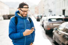 Young bearded hipster guy in blue anorak and cap holding smartphone answering call having happy expression isolated over big city. Background. Stylish man using royalty free stock photos