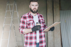Young bearded hipster man,builder, repairman, carpenter, architect, designer dressed in plaid shirt, goggles. Stands in workshop,drinks coffee and holds stock photography