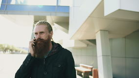 Young bearded hipster man concentrated talking on phone on citystreet, conversation near office building stock video