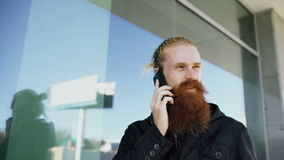 Young bearded hipster man concentrated talking on phone on citystreet and have conversation near office building stock footage