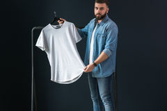 A young bearded hipster man dressed in a denim shirt, stands indoors against the background Royalty Free Stock Image